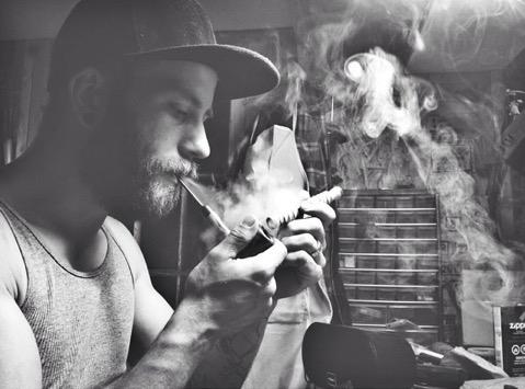 Chris Hildebrand smoking a tobacco pipe in his workshop. Photo credit: Alycia Hildebrand of Alycia Hildebrand Photography.